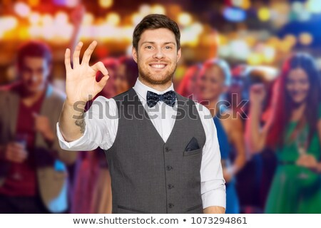 man in suit showing ok sign over night club party Stock photo © dolgachov