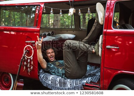 Photo of young hippy man rejoicing and lying in vintage minivan, Stock photo © deandrobot