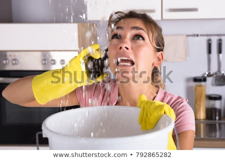 woman calling plumber and collecting water leaking from ceiling stock photo © andreypopov