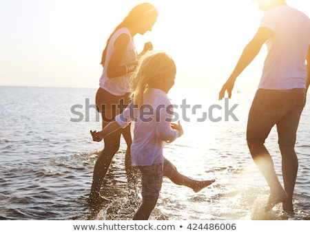 happy father with kids have fun on beach walking at sunset stock photo © dashapetrenko