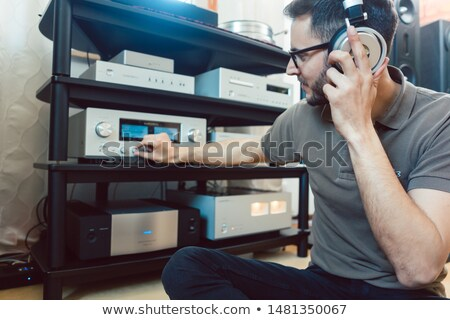 Man turning up the volume on home Hi-Fi stereo Stock photo © Kzenon