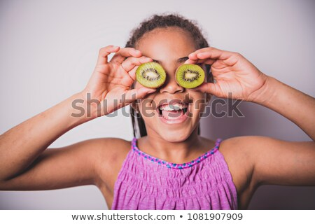 Black girl child with kiwi over the eye ストックフォト © Lopolo