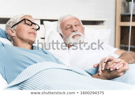 couple sleeping together on bed with white blanket stock photo © andreypopov