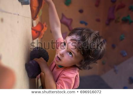 Man climber on artificial climbing wall in bouldering gym Stock photo © galitskaya