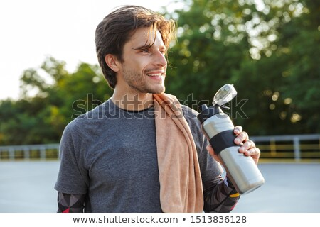 Image of young pleased man in sportswear drinking water and smiling Stock photo © deandrobot