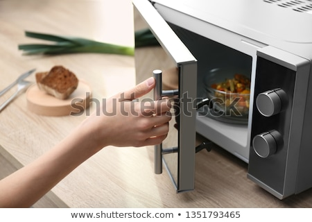 Young Woman Heating Food In Microwave Oven Stock photo © AndreyPopov