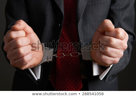 Businessman Wearing Handcuffs Illustrating Corporate Crime Stock photo © HighwayStarz