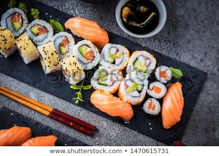 sushi · geserveerd · zwarte · plaat · houten · eetstokjes - stockfoto © m-studio