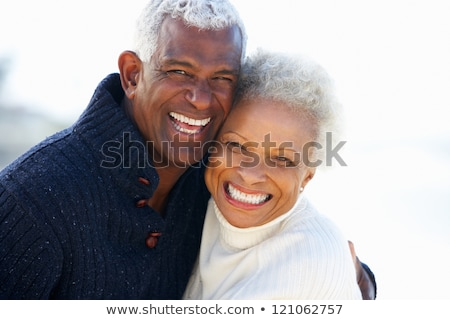smiling couple talking on the beach in autumn stock photo © deandrobot