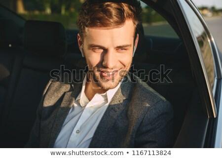 Portrait of happy adult man 30s wearing businesslike suit and ea Stock photo © deandrobot
