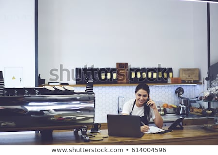 Female owner of cafeteria calling clients and making working notes on paper Stock photo © pressmaster