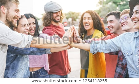 group of smiling friends stacking hands stock photo © dolgachov