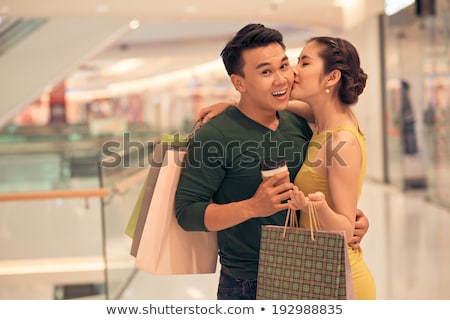 Happy girl with drink and bags and her boyfriend looking at one of departments Stock photo © pressmaster