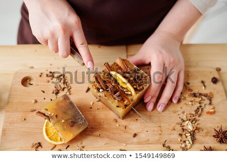 Hands of girl with knife cutting handmade soap bar by table Stock photo © pressmaster