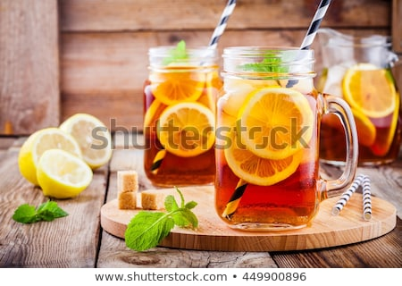 Iced tea with lemon, mint leaves and ice cubes in glass on wet b Stock photo © marylooo