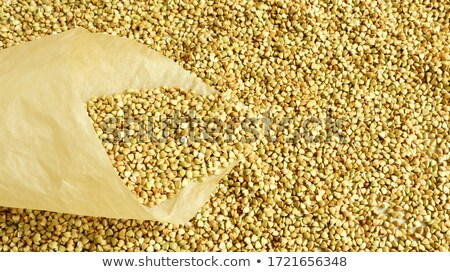 Eco food and dieting concept. Healthy brown buckwheat in bags and wooden spoon, isolated over grey b Stock photo © vkstudio