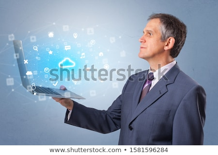 Man holding laptop with cloud based system notifications Stock photo © ra2studio