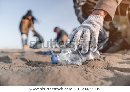 Man in gloves pick up plastic bags that pollute sea. Problem of spilled rubbish trash garbage on the Stock photo © galitskaya