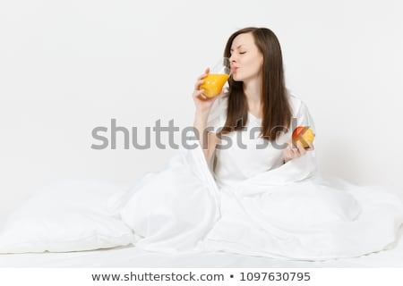 young beautiful woman with apple in bed in the morning stock photo © hasloo