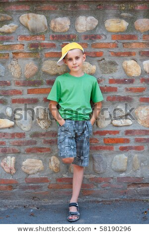 cute young boy with old brick background stock photo © meinzahn
