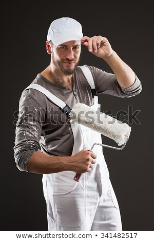Attractive bearded young painter in dungarees standing looking at the camera holding up a roller Stock photo © stryjek