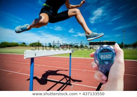 Woman athlete doing hurdles run Stock photo © bluering