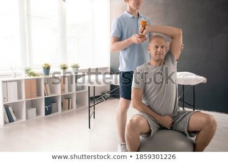 Terapeuta női beteg testmozgás férfi fiatal Stock fotó © AndreyPopov