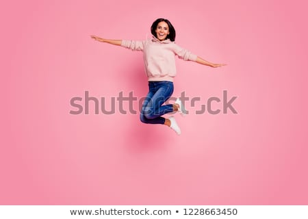 Portrait of an excited girl wearing hoodie jumping Stock photo © deandrobot