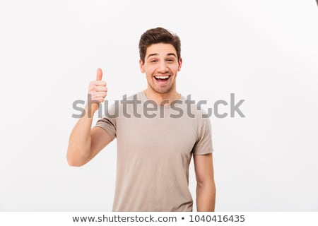 Image of young man 30s having stubble showing thumbs up with hap Stock photo © deandrobot