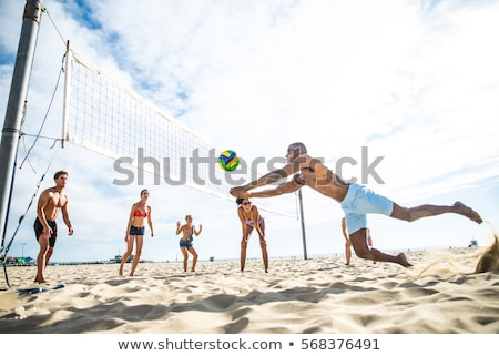 Friends outdoors on the beach play volleyball having fun. Stock photo © deandrobot