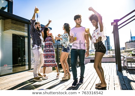 friends having dinner or rooftop party in summer stock photo © dolgachov