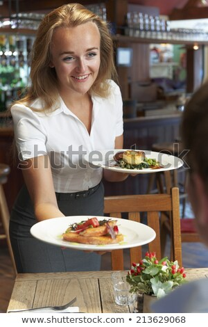 Waitress serving food plate on customers table in restaurant Stock photo © wavebreak_media