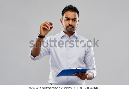 strained indian businessman writing to clipboard Stock photo © dolgachov