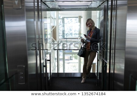Front view of young Caucasian female executive using mobile phone standing in modern office Stock photo © wavebreak_media
