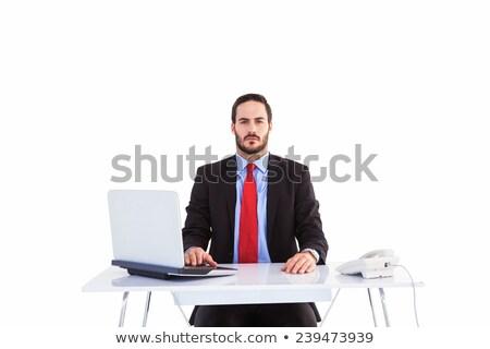 Unsmiling businessman sitting at desk  Stock photo © wavebreak_media