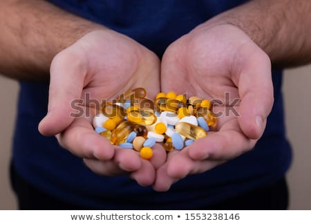 old man with a pile of blue pills in his hand Stock photo © nito