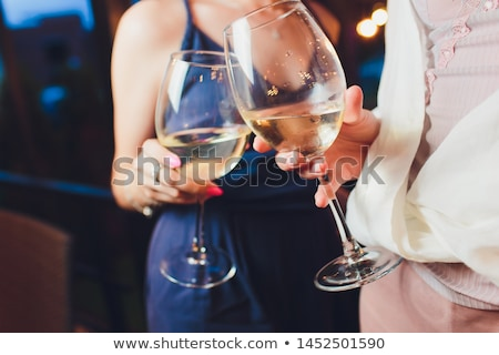 Hands with red wine toasting over served table with food. stock photo © Yatsenko