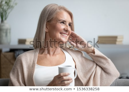 mature woman with cup of tea smiling stock photo © is2