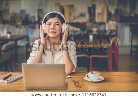 smiling young asian businesswoman listening to music stock photo © deandrobot