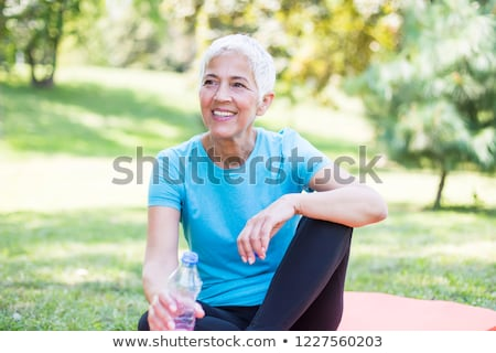 senior sportive woman sitting on mat outside and resting stock photo © boggy