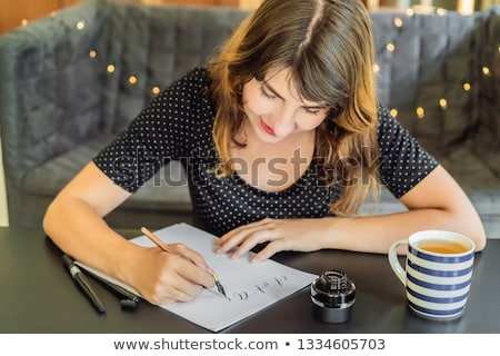 Calligrapher Young Woman writes phrase on white paper. Bible phrase about love Inscribing ornamental Stock photo © galitskaya