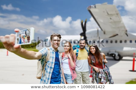 friends taking selfie over plane on airfield Stock photo © dolgachov