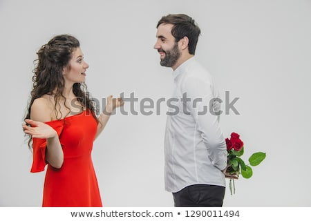 woman and man with bunch of roses behind his back Stock photo © dolgachov