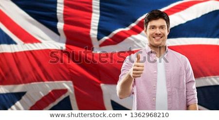 happy man showing thumbs up over british flag Stock photo © dolgachov