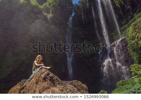 Woman in turquoise dress at the Sekumpul waterfalls in jungles on Bali island, Indonesia. Bali Trave Stock photo © galitskaya