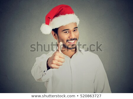 Optimistic happy young man in christmas santa hat Stock photo © deandrobot
