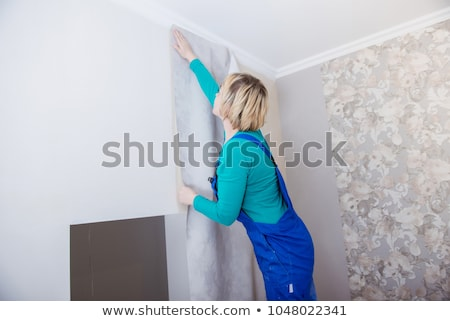 Young woman putting up wallpaper Stock photo © photography33