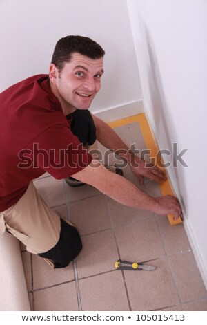 Man putting down tape around the edge of a tiled floor Stock photo © photography33