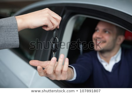 Stock photo: Man receiving car keys while sitting in his car in a garage