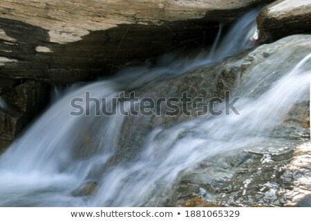 Icicles on stone and flowing water Stock photo © Anettphoto